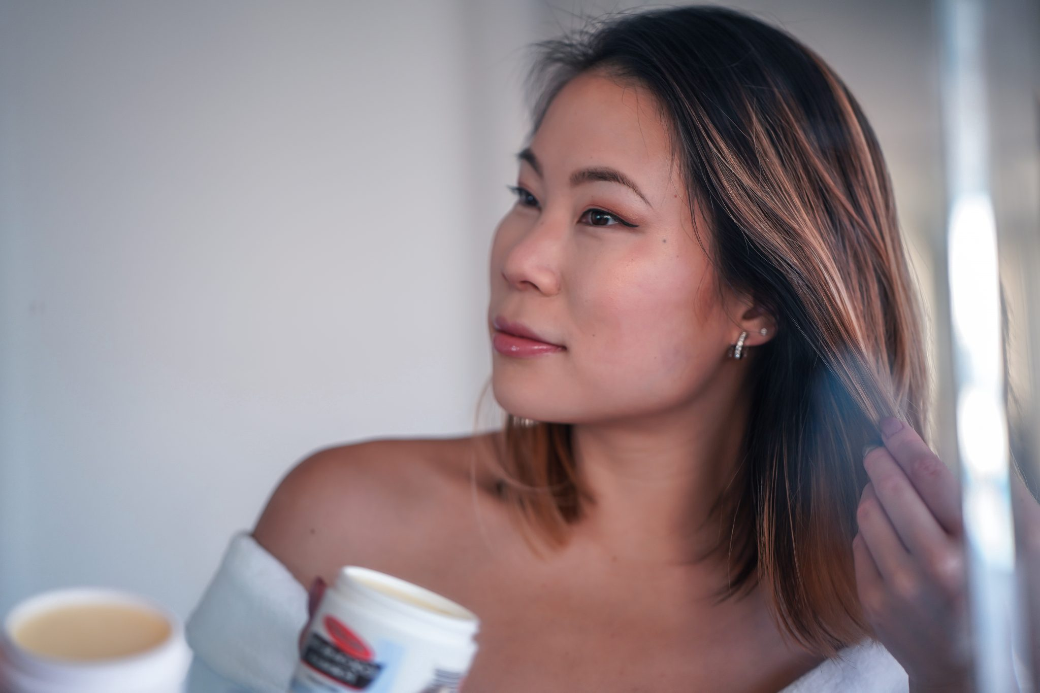 Kasey Ma Beauty Influencer of TheStyleWright Applies Palmer's Coconut Butter Formula to tame fly-aways In her hair for dry skincare